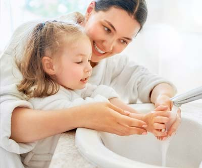 Mother helping daughter wash hands